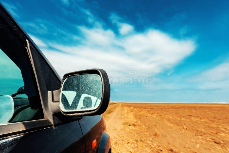 Vingspegel av en bil på smutslandsvägen royaltyfria bilder