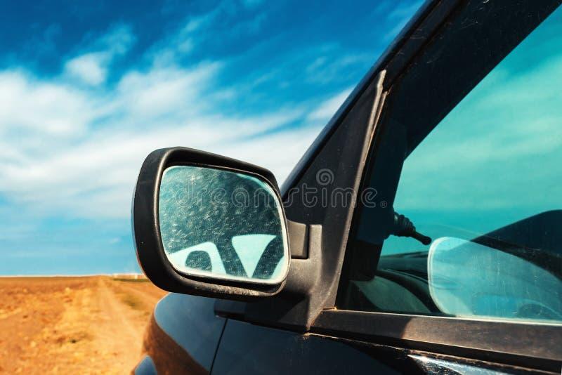 Vingspegel av en bil p? smutslandsv?gen arkivbild