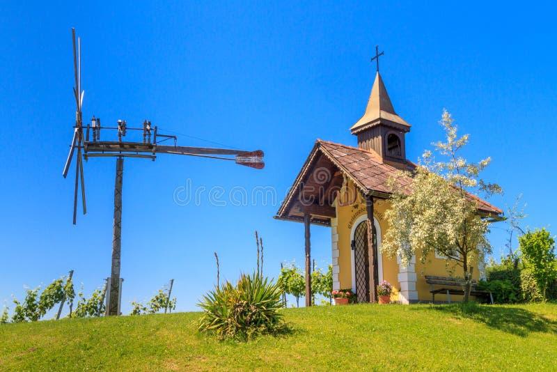 Vinhedo de Styrian Toscânia com capela e o moinho de vento pequenos, Styria, foto de stock
