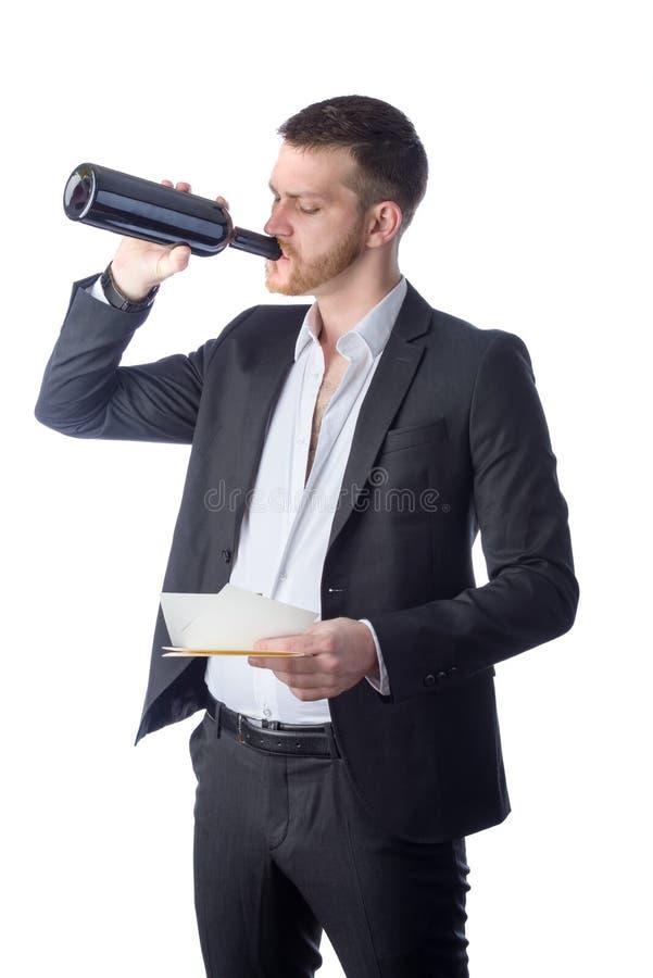 Vinho bebendo do homem de negócios frustrante e vista de papéis foto de stock
