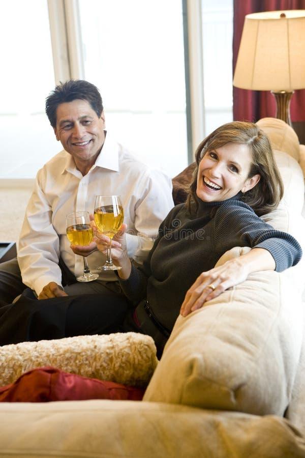 Vinho bebendo dos pares maduros junto no sofá imagem de stock royalty free