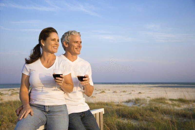 Vinho bebendo dos pares na praia imagem de stock
