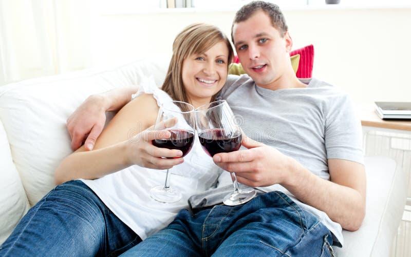 Vinho bebendo dos pares novos bonitos no sofá fotografia de stock