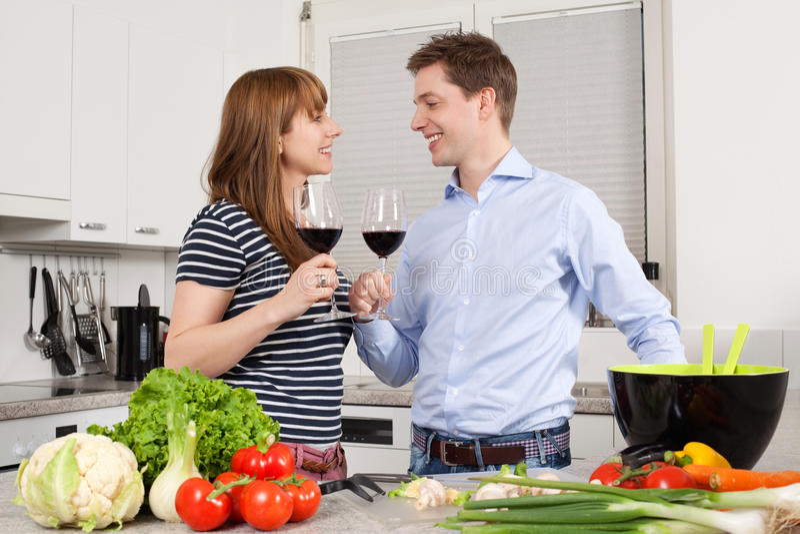 Vinho bebendo dos pares novos na cozinha foto de stock royalty free