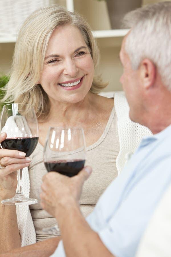 Vinho bebendo dos pares sênior felizes em casa fotos de stock royalty free