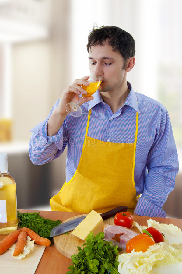 Vinho branco de cozimento e bebendo do homem fotografia de stock