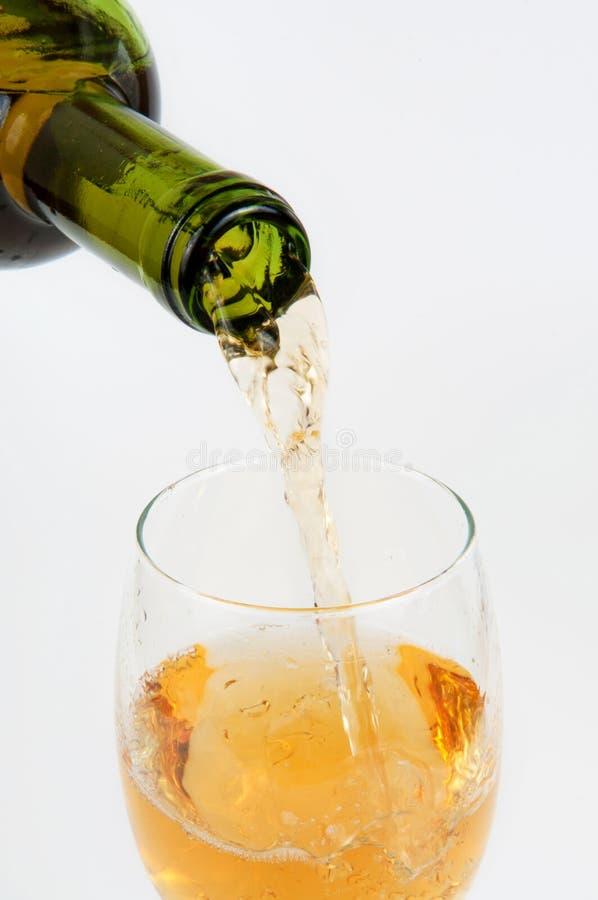 Vinho branco de derramamento da garrafa no copo de vinho fotos de stock