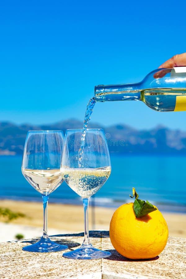Vinho branco de derramamento do garçom em vidros de vinho no mar azul do witn exterior do terraço e em Mountain View no fundo fotografia de stock