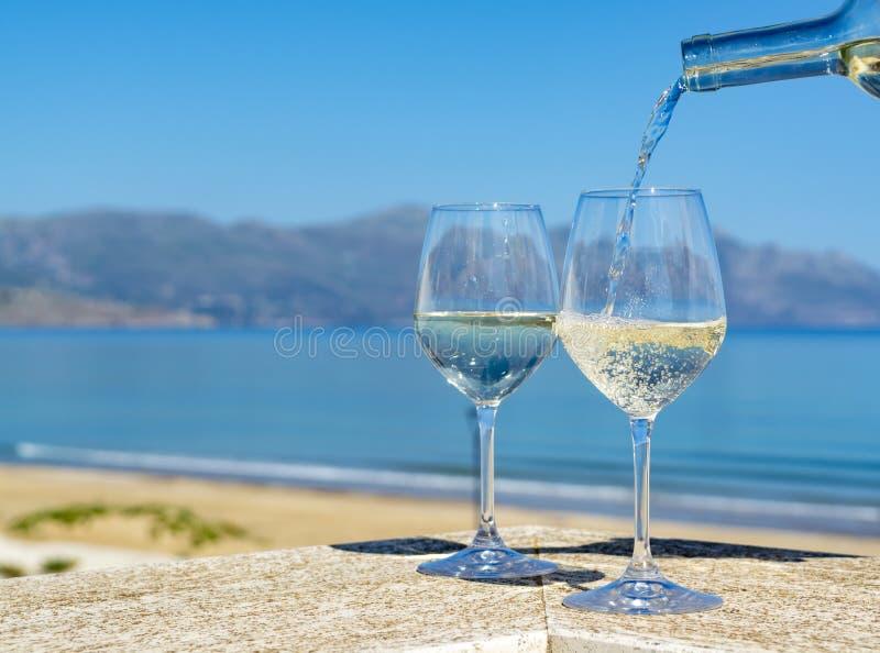Vinho branco de derramamento do garçom em vidros de vinho no mar azul do witn exterior do terraço e em Mountain View no fundo fotos de stock