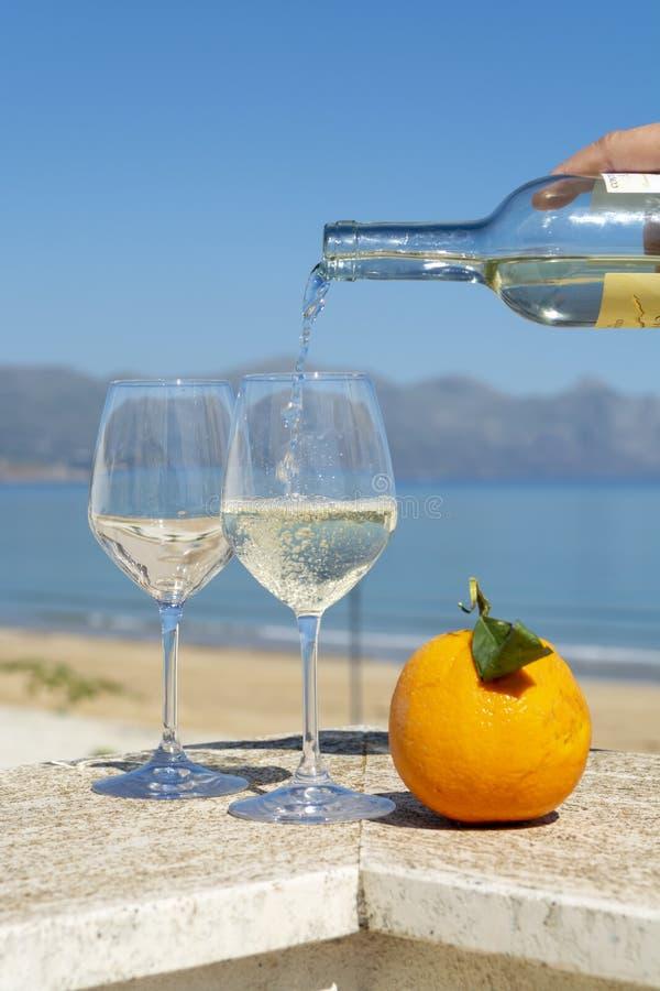 Vinho branco de derramamento do garçom em vidros de vinho no mar azul do witn exterior do terraço e em Mountain View no fundo imagem de stock royalty free