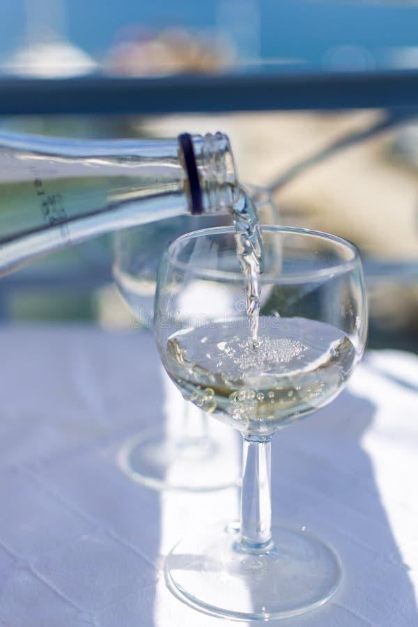 Vinho branco de derramamento do garçom no vidro na tabela do terraço com opinião do mar fotografia de stock
