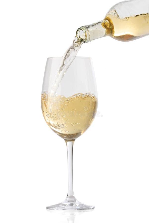 Vinho branco de derramamento em um vidro imagem de stock