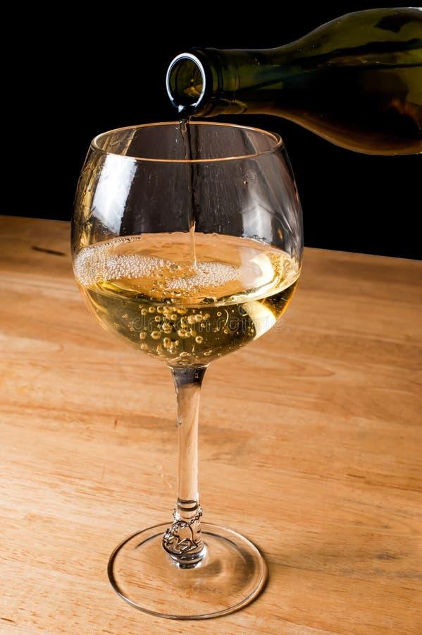 Vinho branco de derramamento em um wineglass fotos de stock