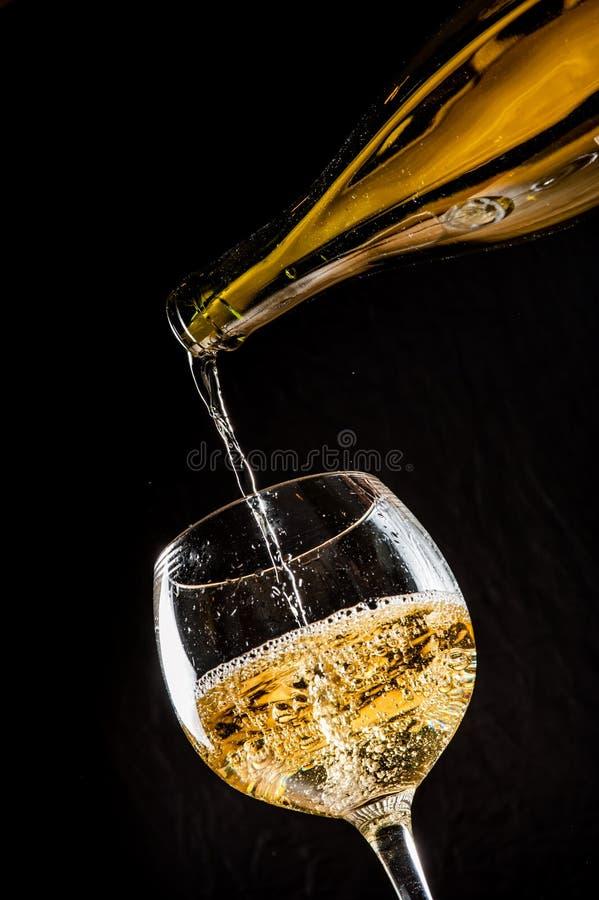 Vinho branco de derramamento em um wineglass fotografia de stock