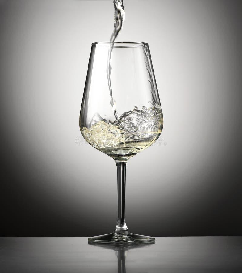 Vinho branco de derramamento em um wineglass fotos de stock royalty free