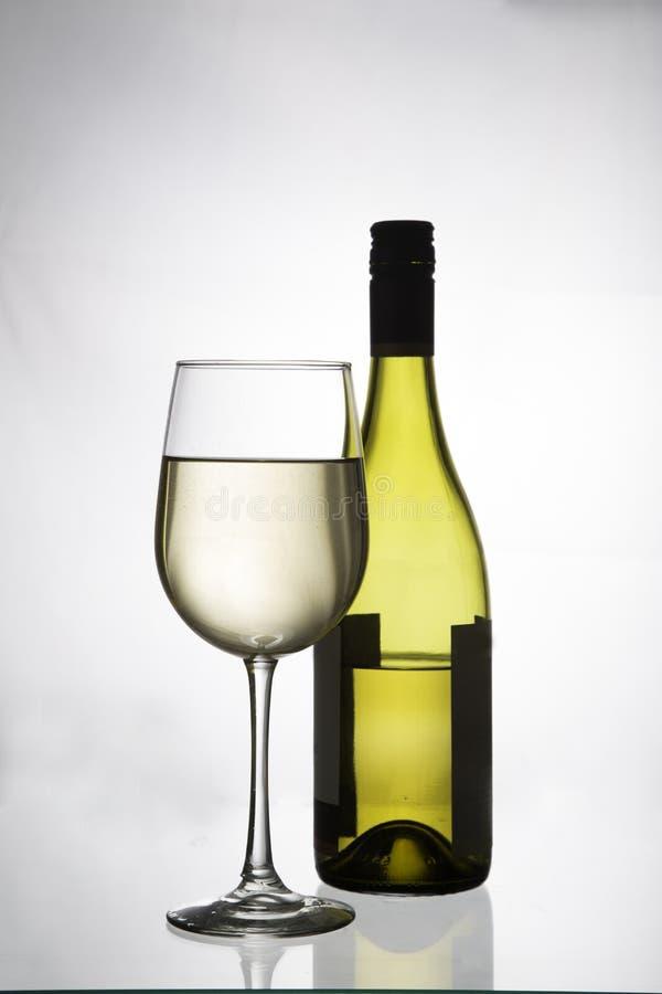 Vinho branco em um vidro e em uma garrafa fotos de stock