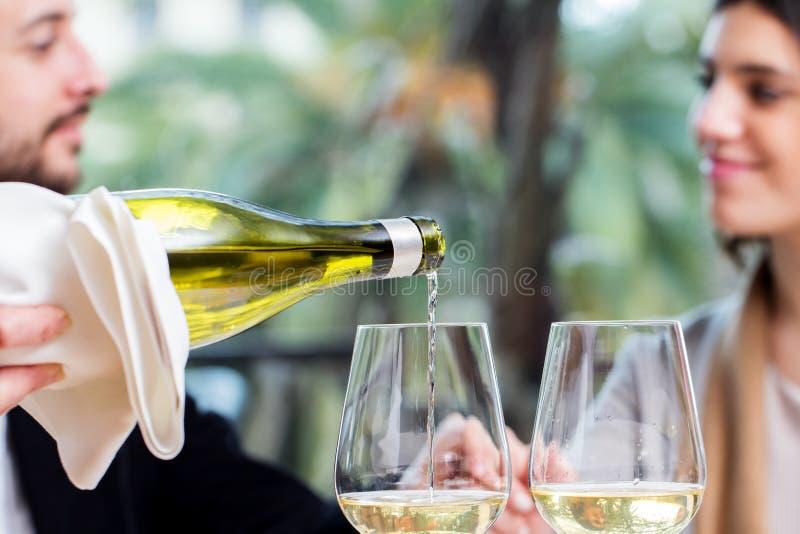 Vinho branco que derrama com pares no fundo fotografia de stock