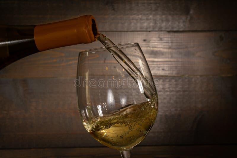 Vinho branco que derrama no vidro fotografia de stock