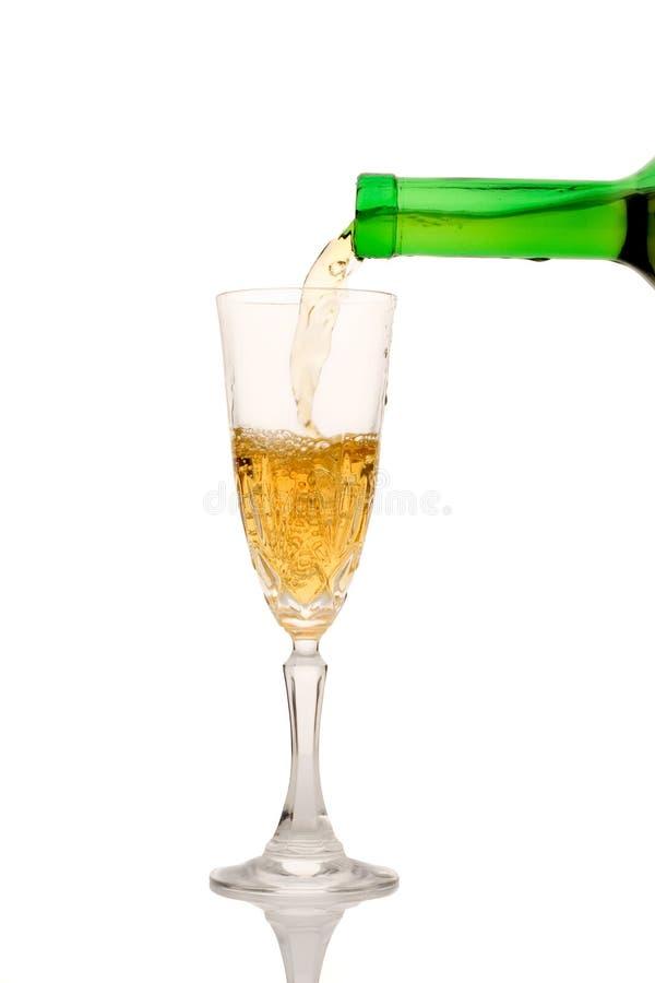 Vinho branco que derrama para baixo de um frasco (trajeto de grampeamento incluído) fotografia de stock