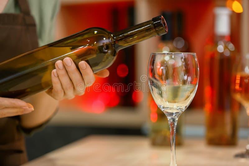 Vinho de derramamento do empregado de bar fêmea da garrafa no vidro no contador imagem de stock