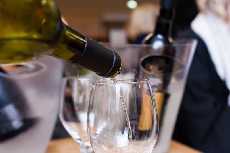 Vinho de derramamento do garçom em um vidro foto de stock