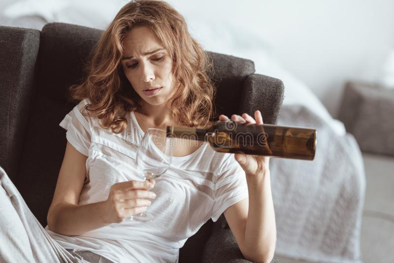 Vinho de derramamento forçado da mulher em casa imagens de stock