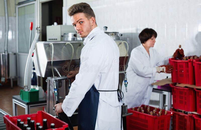 Vinho de engarrafamento do trabalhador masculino com a máquina na fábrica do vinho espumante imagens de stock
