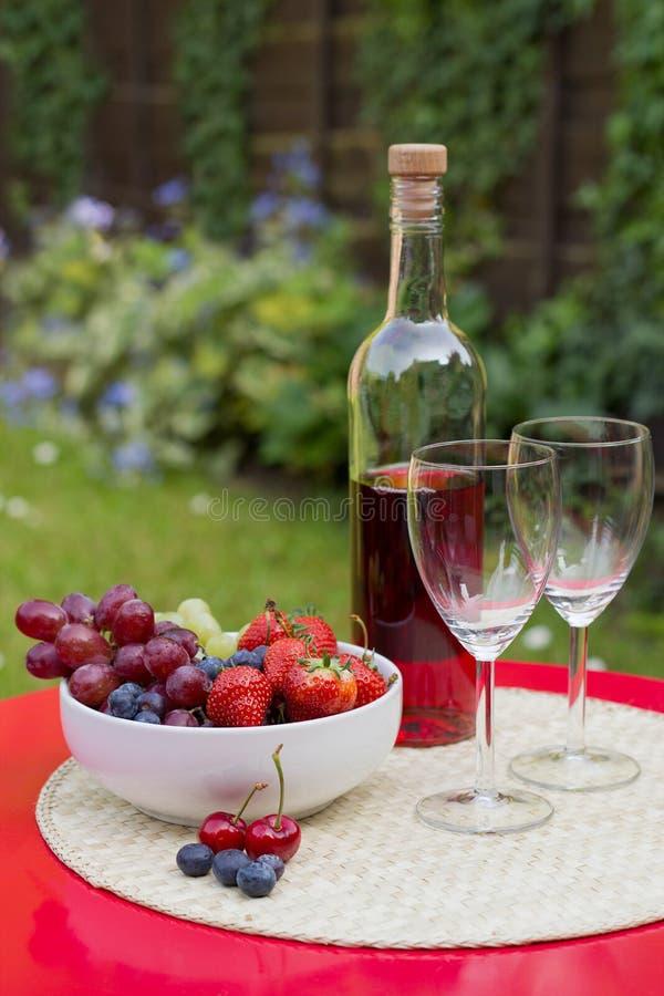 Vinho de Rosa com frutas do verão na tabela do jardim imagens de stock royalty free