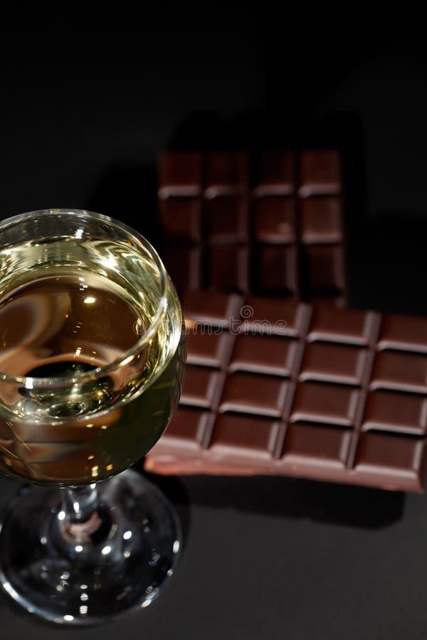 Vinho e chocolate Abrandamento luxuoso da noite com um vidro do wh foto de stock