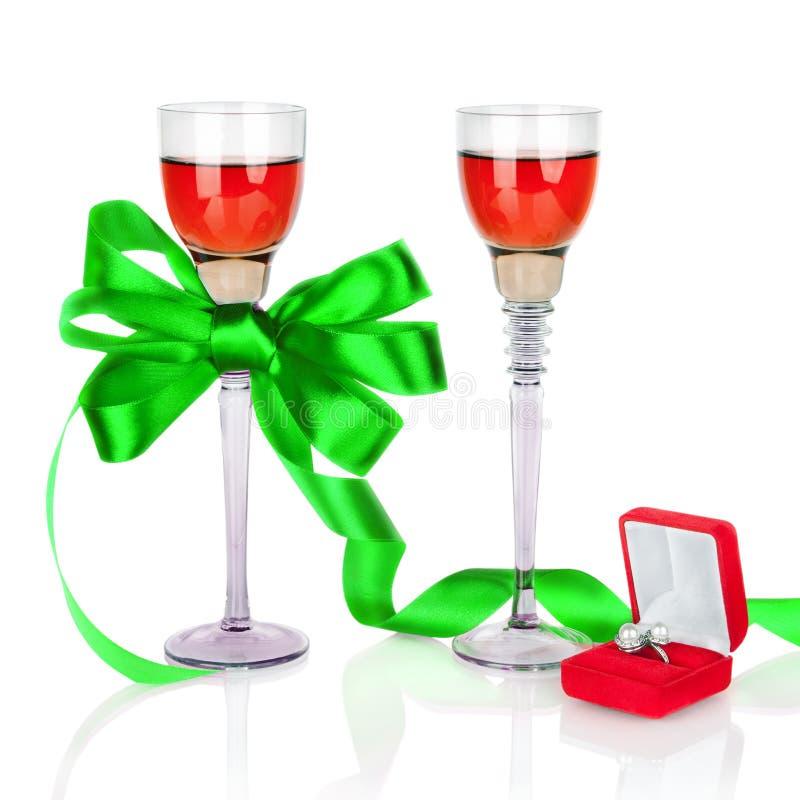 Vinho em dois wineglasses com curva e alianças de casamento verdes do cetim foto de stock