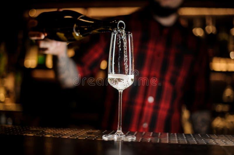 Vinho espumante de derramamento do empregado de bar, em um vidro elegante imagem de stock