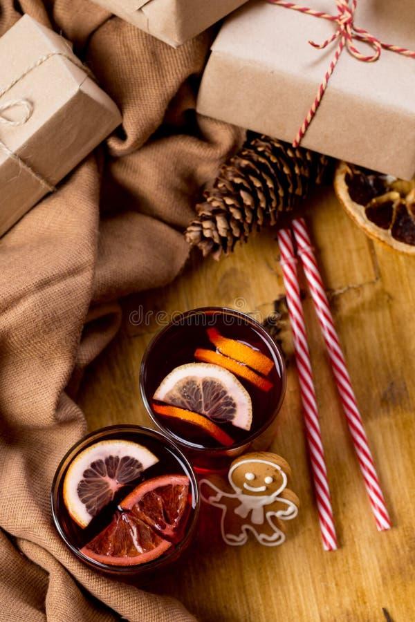 Vinho ferventado com especiarias na caneca de vidro com especiarias Bebida quente do Natal na tabela de madeira com presentes do  fotografia de stock