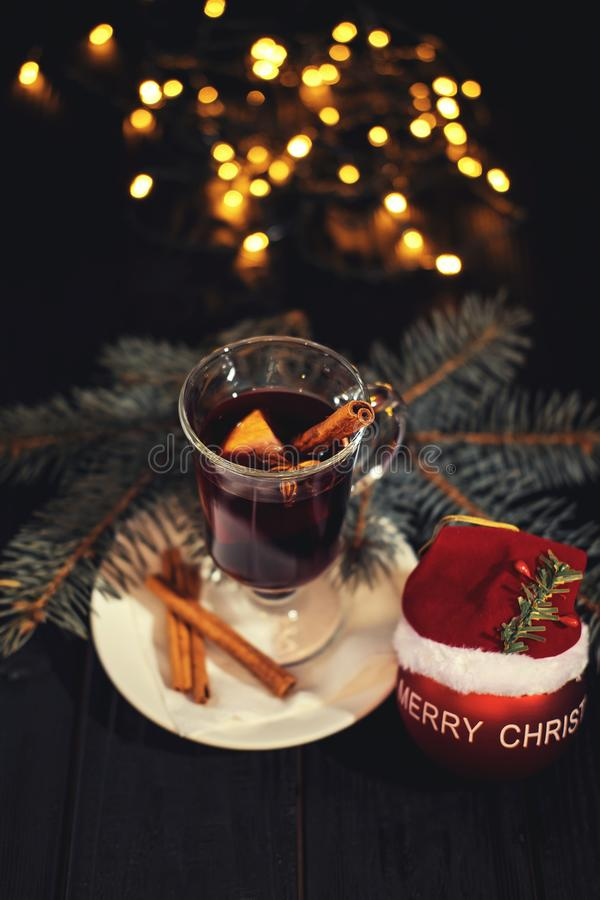 Vinho ferventado com especiarias na placa branca na tabela, em varas de canela e na laranja de madeira pretas, bola do Natal fotos de stock royalty free