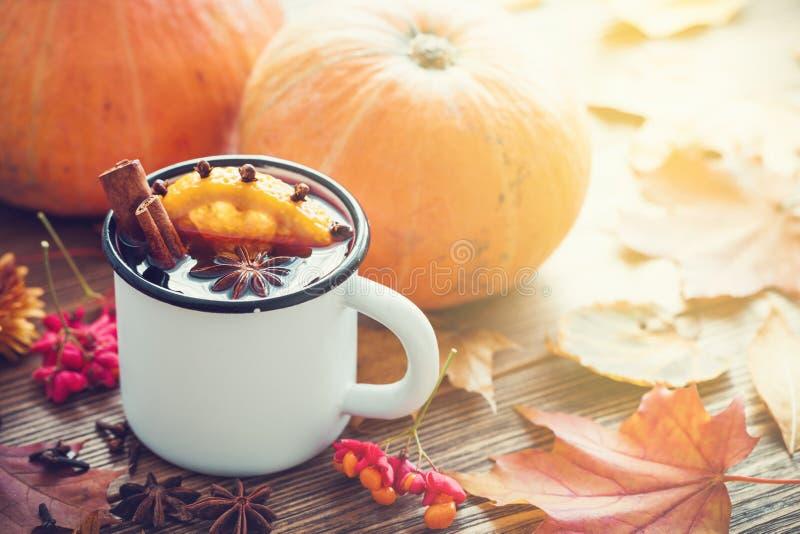 Vinho ferventado com especiarias no copo e em abóboras esmaltados na tabela com folhas de outono fotografia de stock royalty free