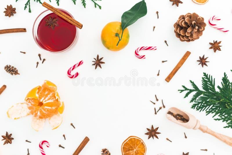 Vinho ferventado com especiarias quente do Natal com o bastão da canela, do anis e de doces no fundo branco Composição do quadro  fotografia de stock