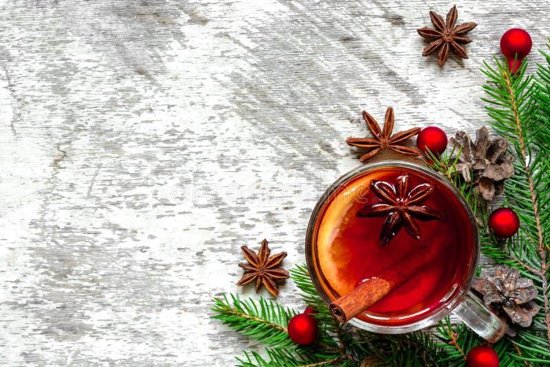 Vinho ferventado com especiarias quente do Natal com ramos de árvore da canela, do anis e do abeto no fundo de madeira branco imagens de stock royalty free