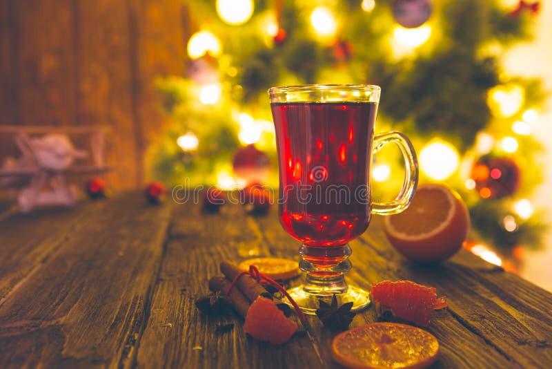 Vinho ferventado com especiarias quente com especiarias e árvore de Natal no fundo de madeira Conceito do Natal ou do ano novo imagens de stock royalty free