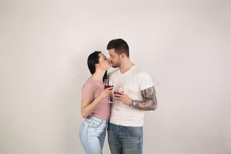 Vinho moreno bonito da bebida dos pares e beijo na frente de um fundo branco Um homem com uma tatuagem fresca disponível foto de stock royalty free