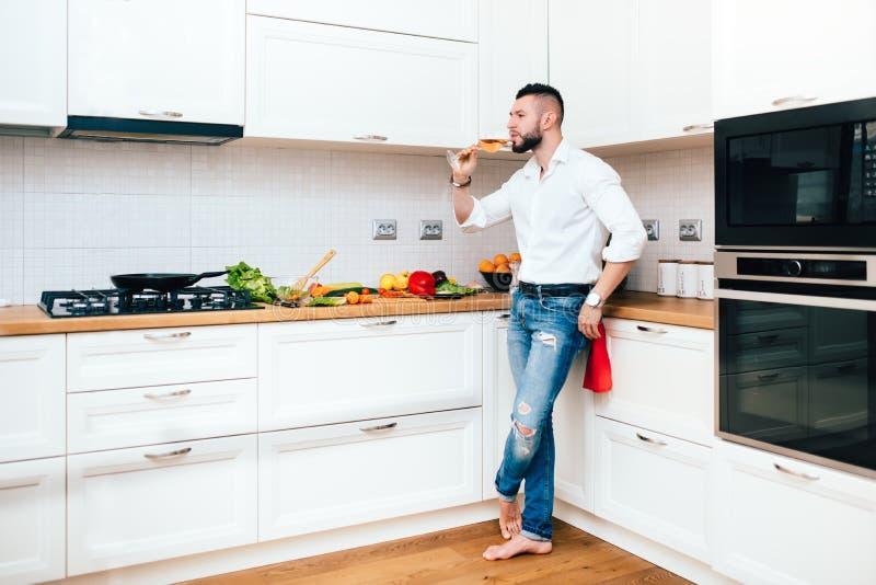 Vinho profissional do gosto do cozinheiro chefe antes do jantar Cozinheiro masculino que prepara o alimento e que bebe o vinho fotografia de stock