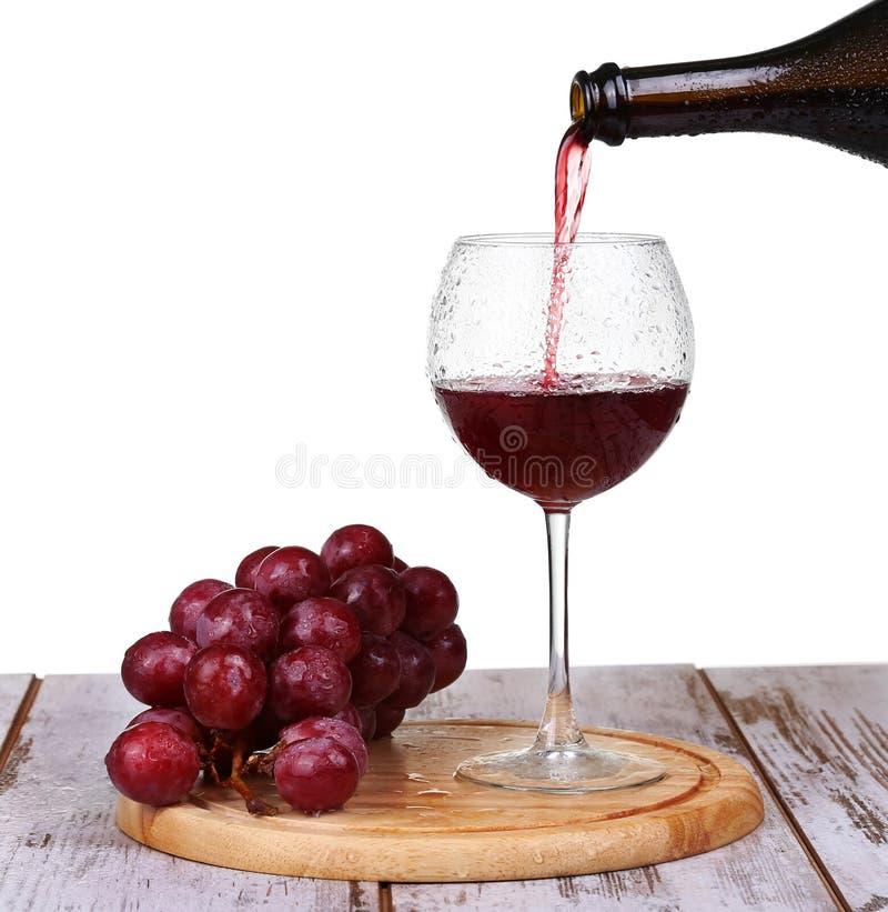 Vinho que derrama no vidro com uva e frascos fotografia de stock royalty free