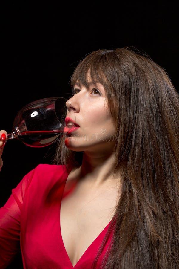 Vinho tinto bebendo da jovem mulher de um vidro fotos de stock