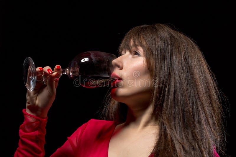 Vinho tinto bebendo da jovem mulher de um vidro imagens de stock