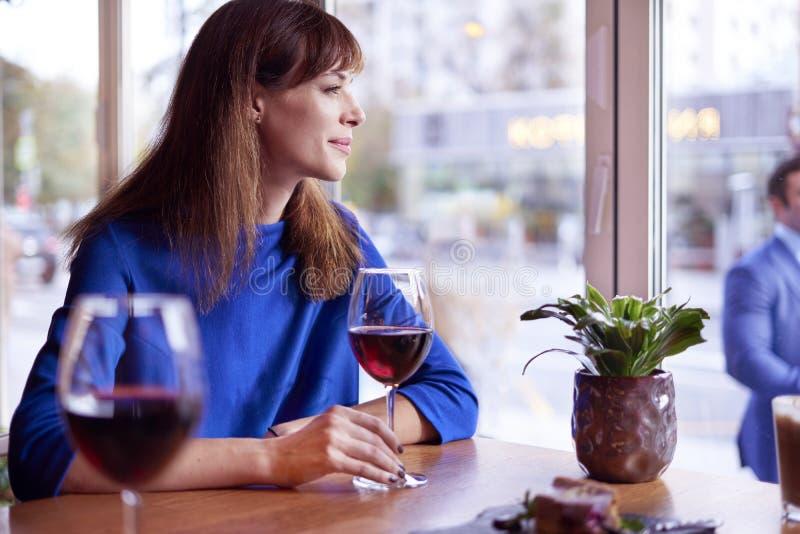 Vinho tinto bebendo da mulher bonita no café perto da janela relógios de senhora na janela no indivíduo no terno azul fotos de stock royalty free