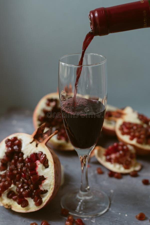 Vinho tinto com uma romã aberta em um fundo concreto cinzento textured Um homem derrama o vinho tinto de uma garrafa foto de stock
