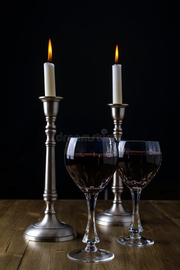 Vinho tinto com velas na tabela de madeira fotografia de stock