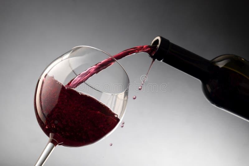 Vinho tinto de derramamento da garrafa no copo de vinho imagem de stock