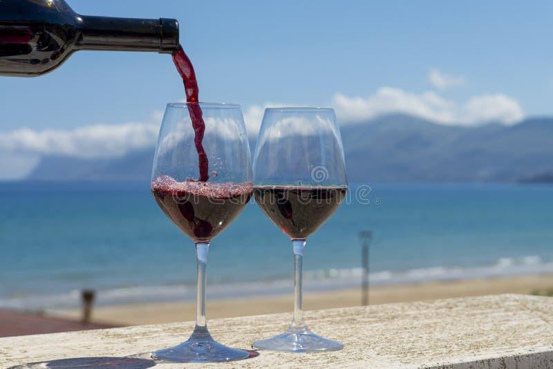 Vinho tinto de derramamento do garçom em vidros de vinho no mar azul do witn exterior do terraço e em Mountain View no fundo imagem de stock royalty free