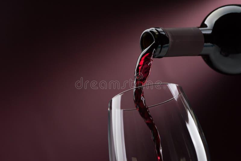 Vinho tinto de derramamento em um copo de vinho imagem de stock royalty free