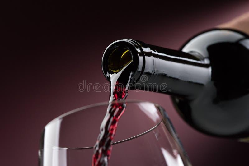 Vinho tinto de derramamento em um copo de vinho fotos de stock royalty free