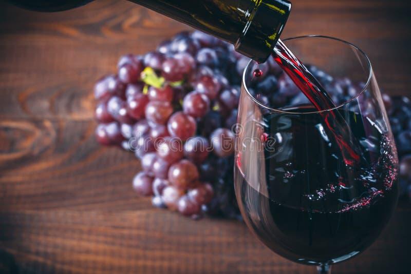Vinho tinto de derramamento no vidro com um grupo de uvas vermelhas foto de stock royalty free